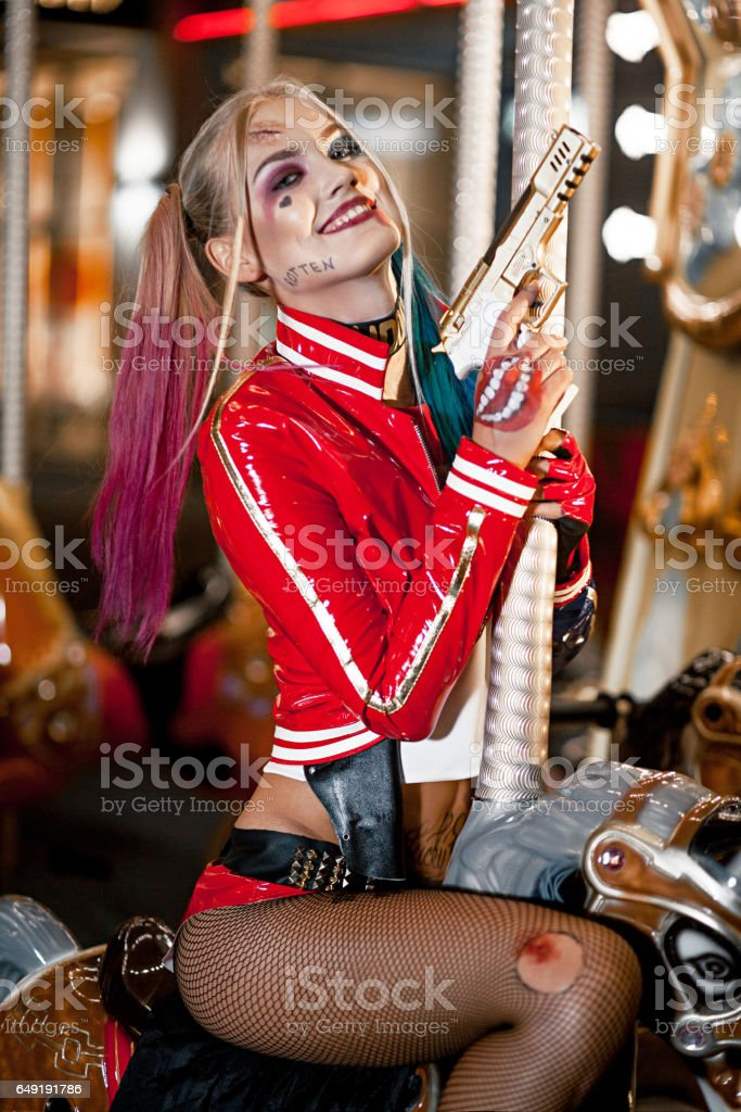 Portrait of smiling cosplayer girl in costume Harley Quinn on background lights of carousel ride. stock photo