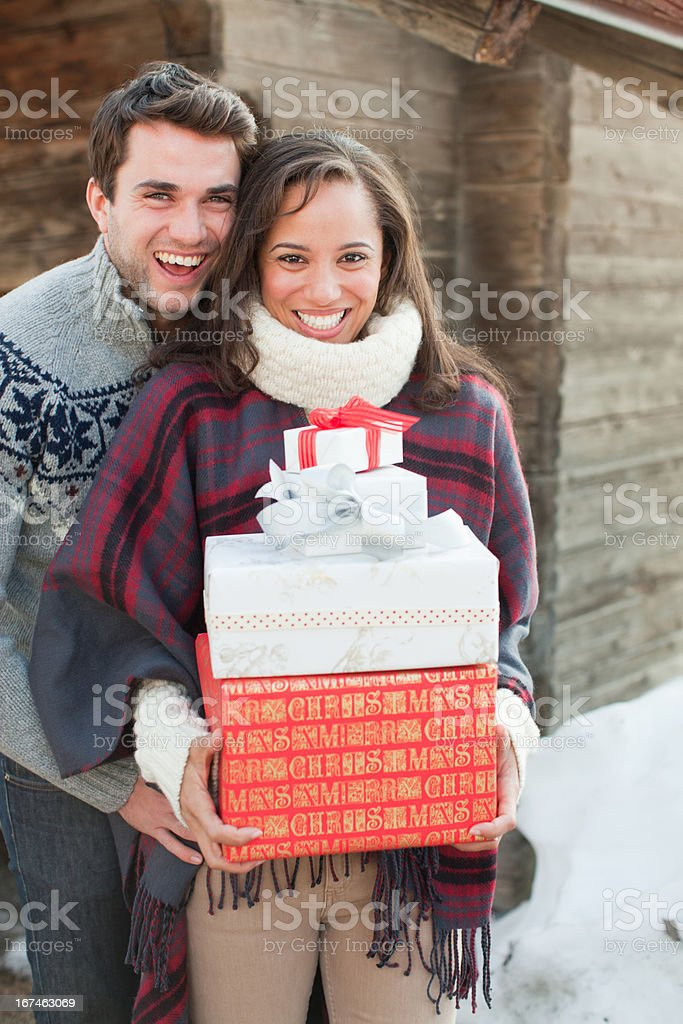 Portrait of smiling couple holding Christmas gifts in front of cabin stock photo