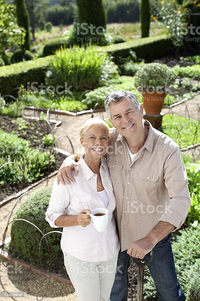 Portrait of smiling couple holding teacup in domestic garden royalty-free stock photo