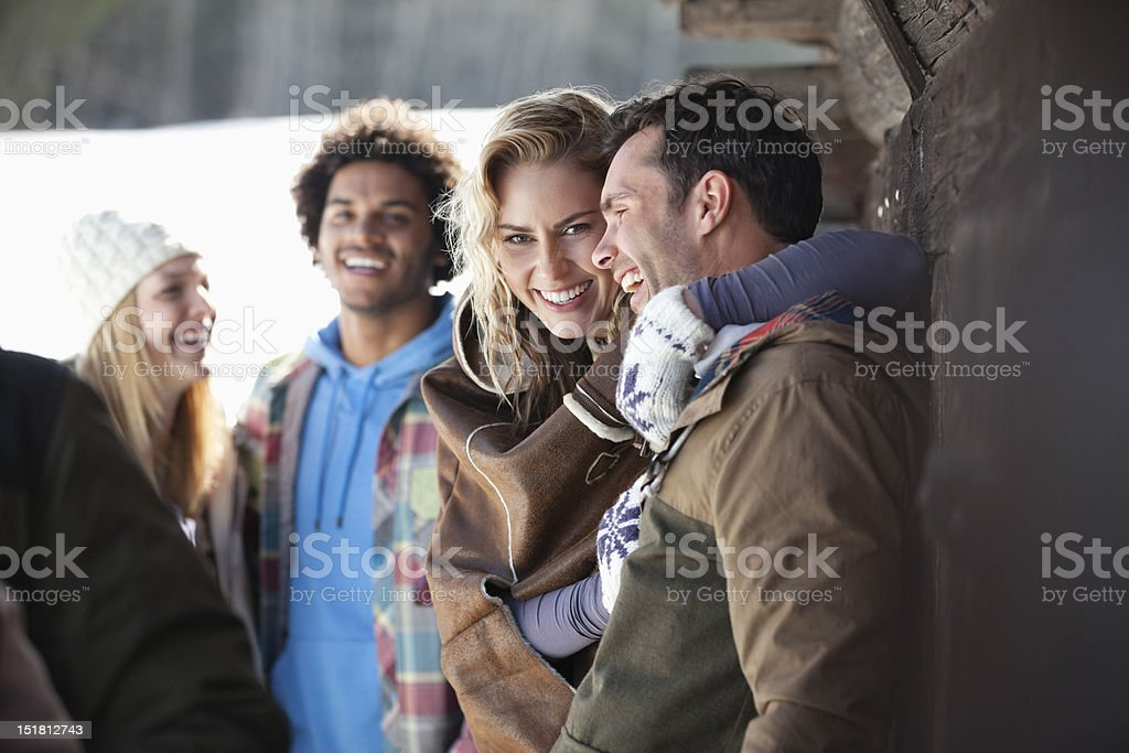 Portrait of smiling couple hugging outside cabin royalty-free stock photo