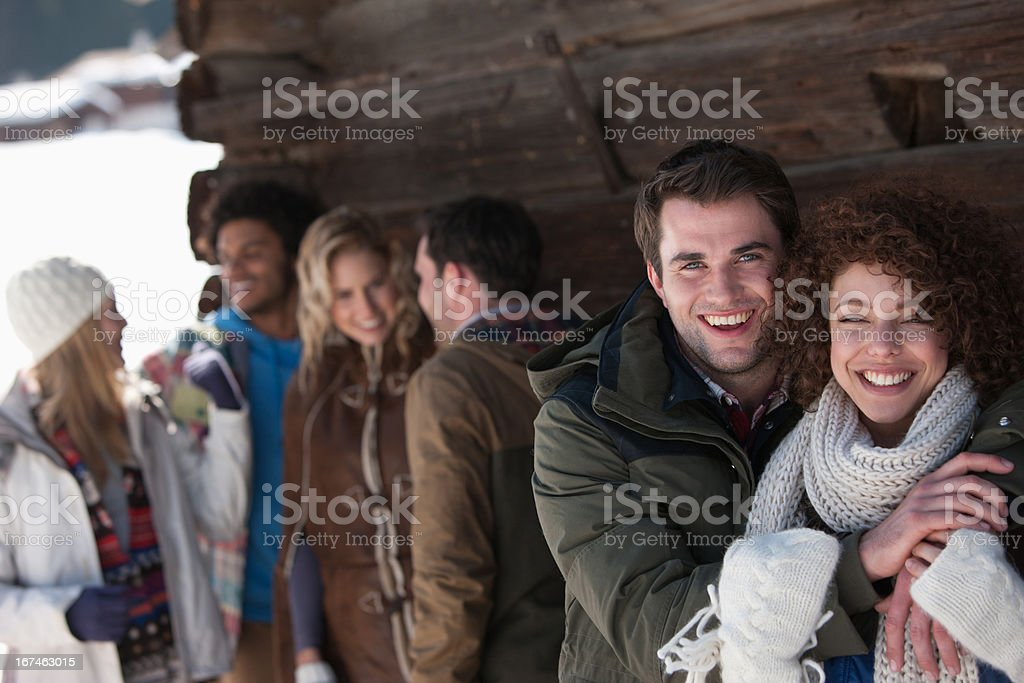 Portrait of smiling couple hugging with friends in background royalty-free stock photo