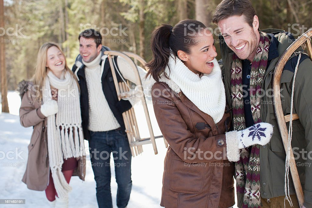 Portrait of smiling couple with sled in snowy woods stock photo