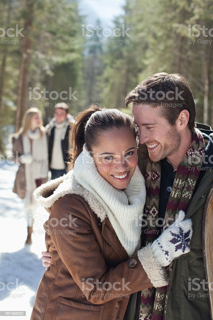 Portrait of smiling couple with sled in snowy woods royalty-free stock photo