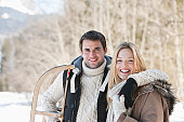 Portrait of smiling couple with sled in woods