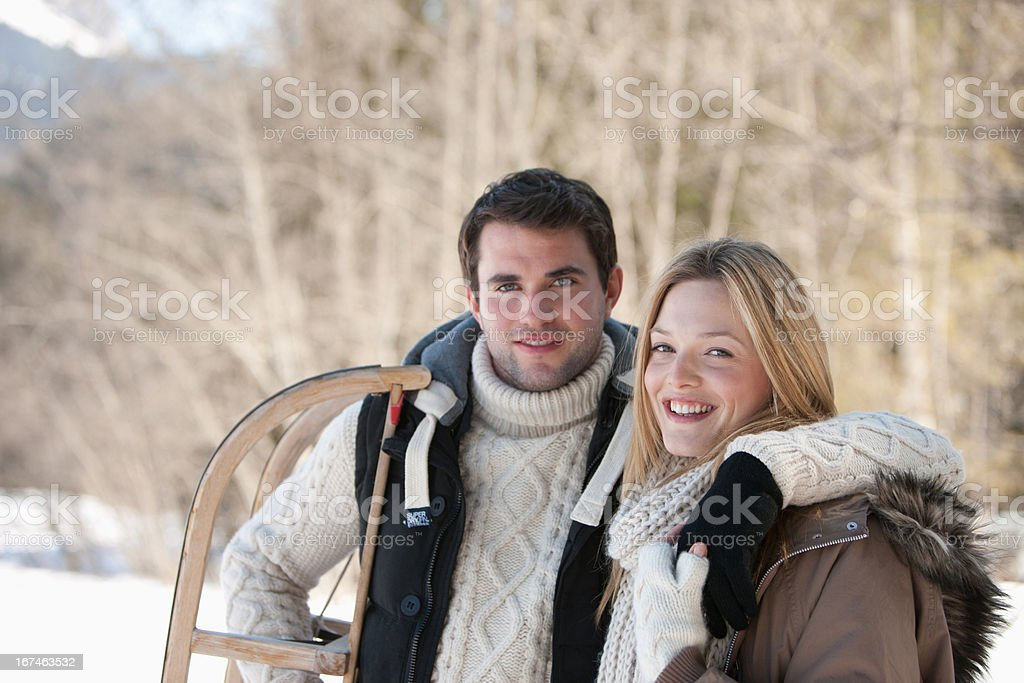 Portrait of smiling couple with sled in woods stock photo