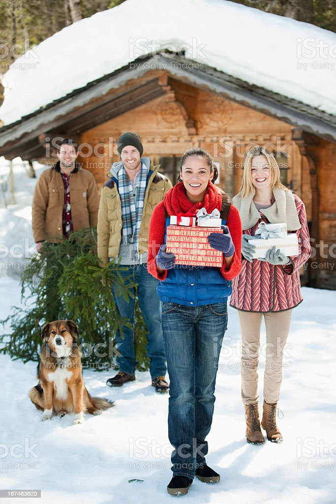 Portrait of smiling couples and dog with fresh cut Christmas tree and gifts in front of cabin royalty-free stock photo