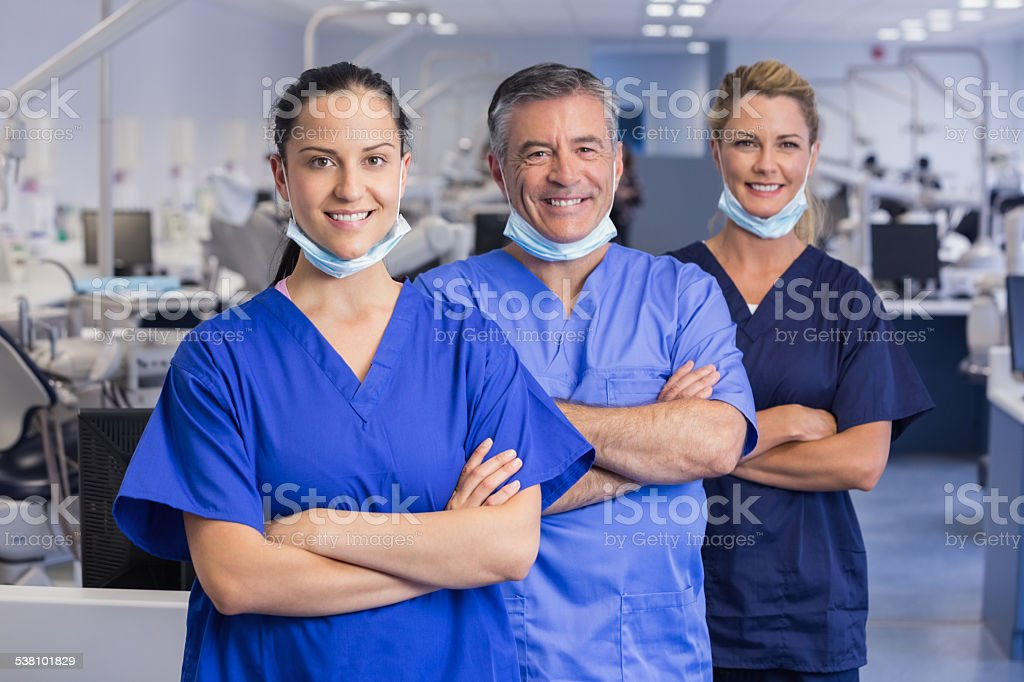 Portrait of smiling co-workers in a line with arms crossed stock photo