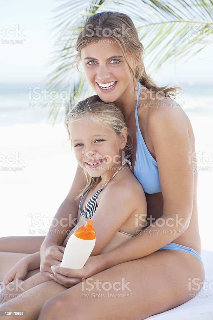 Portrait of smiling daughter with mother holding suntan lotion royalty-free stock photo