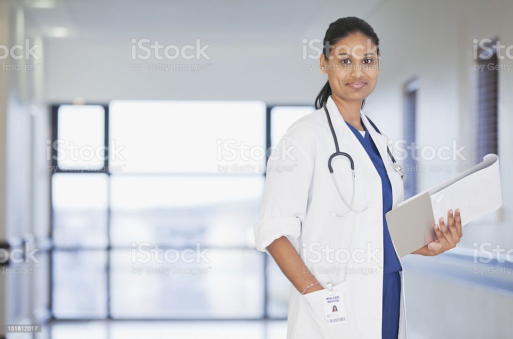 Portrait of smiling doctor with notepad in hospital corridor stock photo