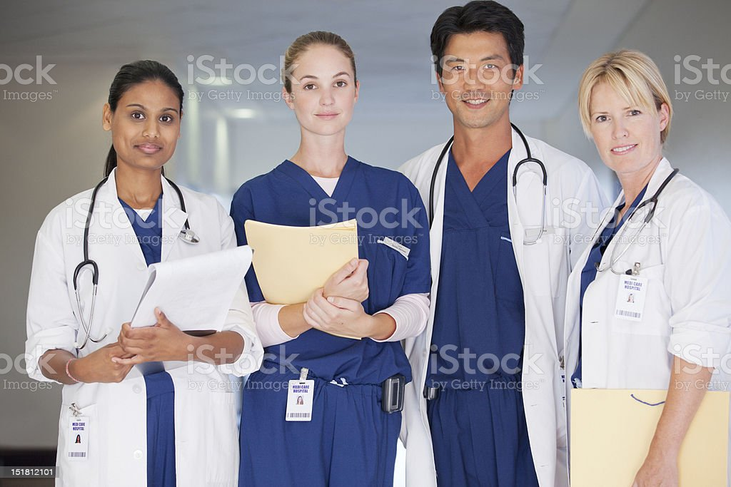 Portrait of smiling doctors and nurse holding medical records in hospital corridor royalty-free stock photo