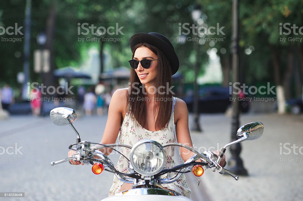Portrait of smiling fashion girl riding a retro scooter stock photo