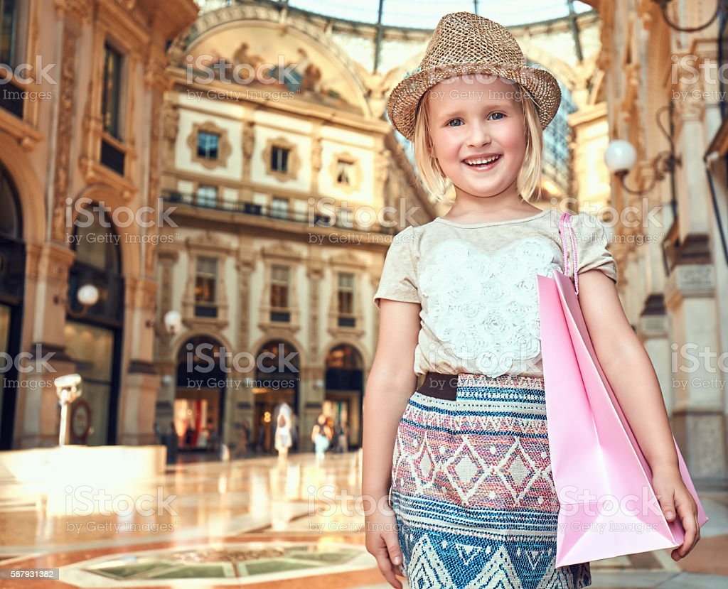 Portrait of smiling fashion girl with shopping bag in Galleria stock photo