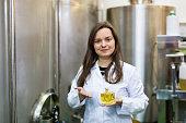 Portrait of smiling female engineer holding perfume oil bottle