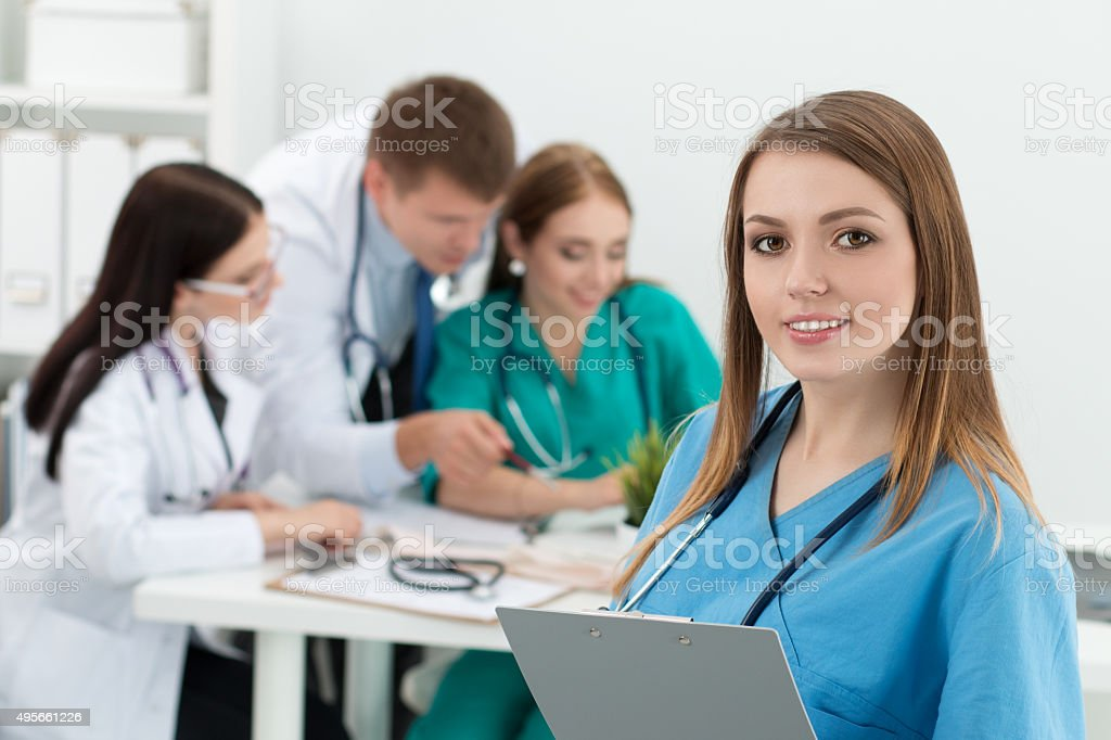Portrait of smiling female medicine doctor holding folder with d stock photo