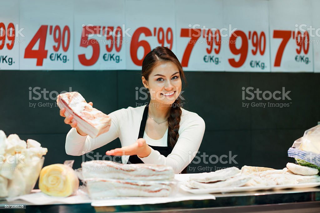 Portrait of smiling female seller offering salo and lard stock photo