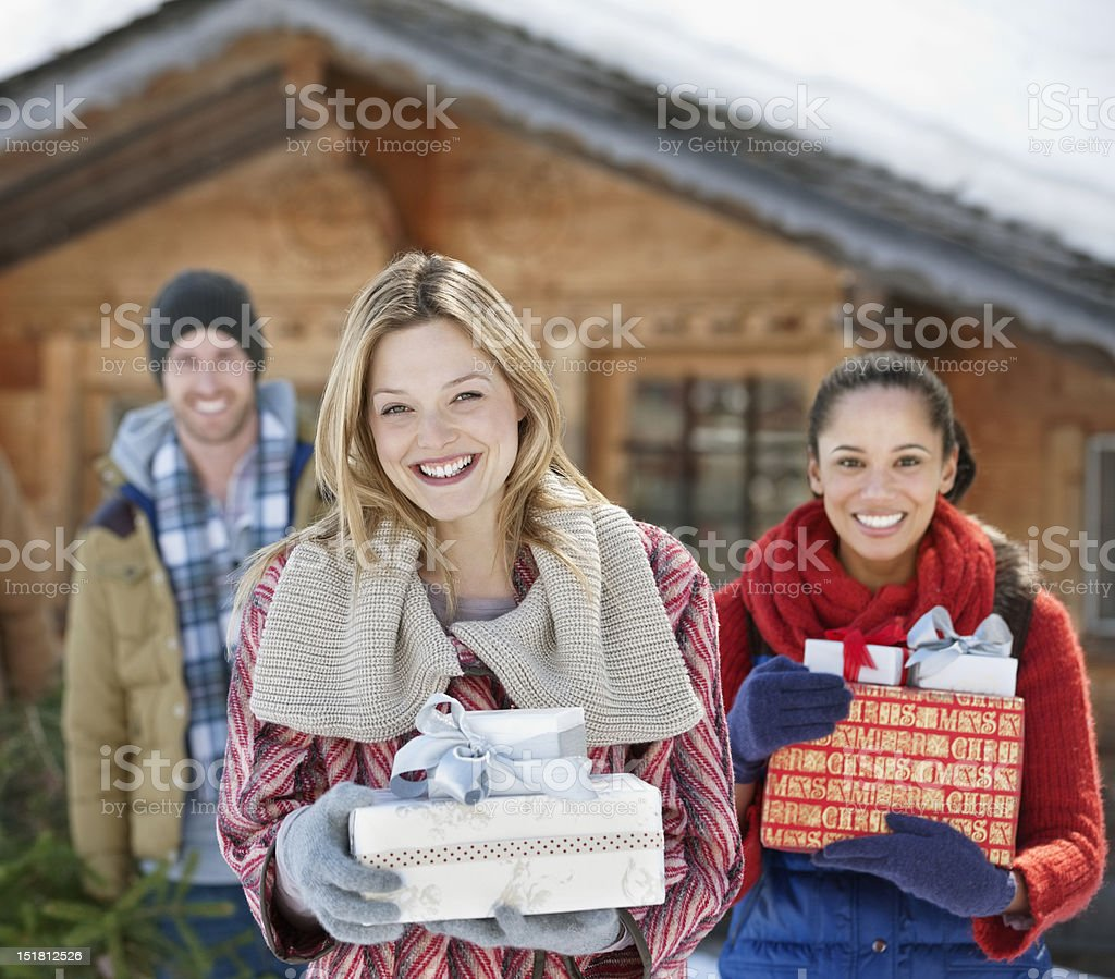 Portrait of smiling friends holding Christmas gifts in front of cabin royalty-free stock photo