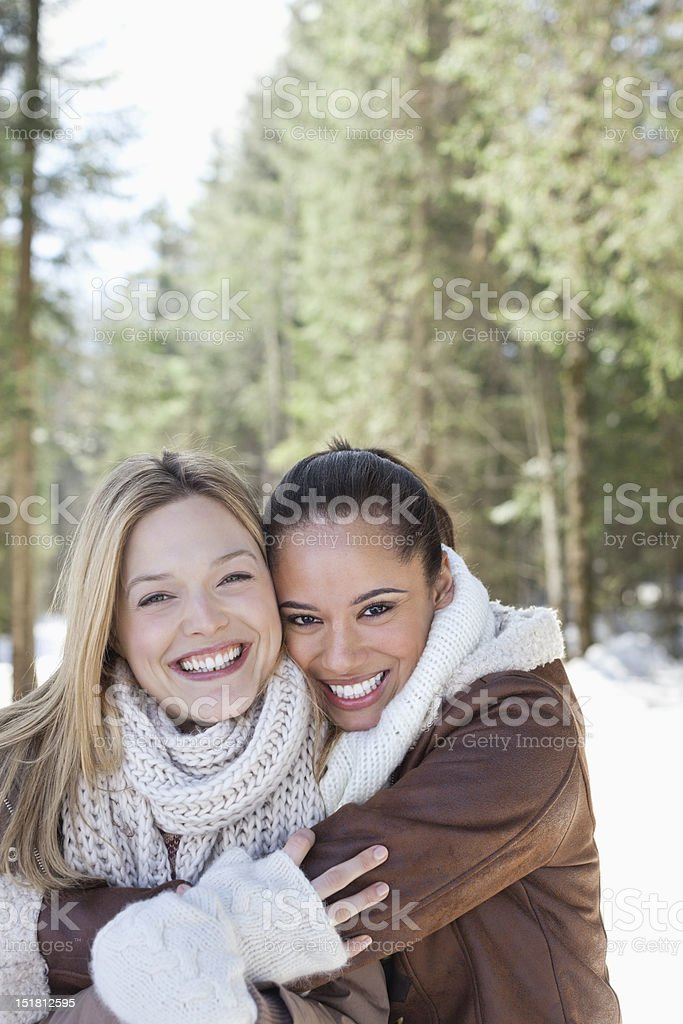 Portrait of smiling friends hugging in snowy woods royalty-free stock photo