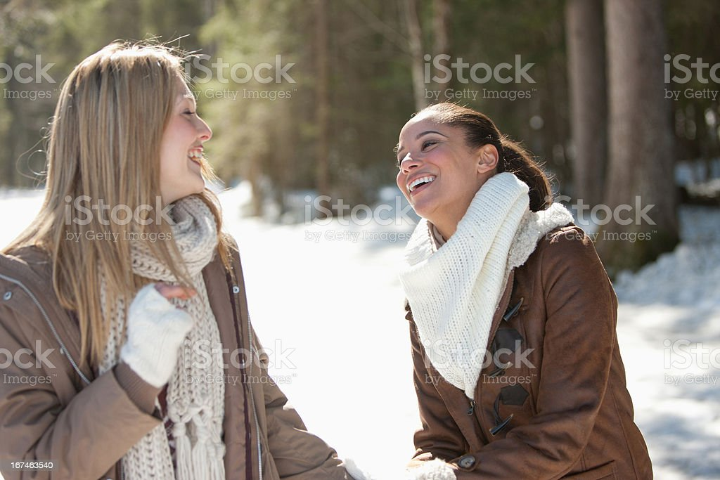 Portrait of smiling friends hugging in snowy woods stock photo
