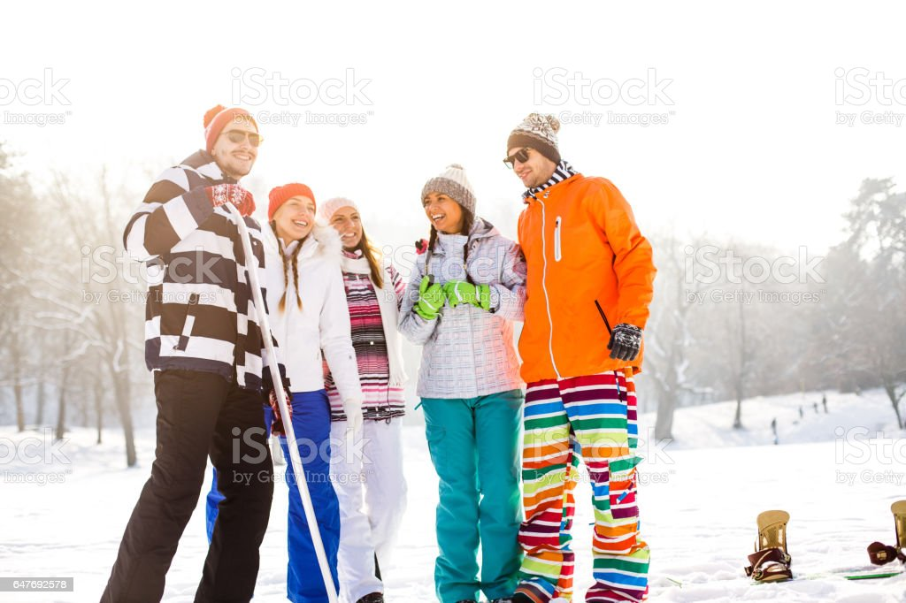 Portrait of smiling friends in snow stock photo