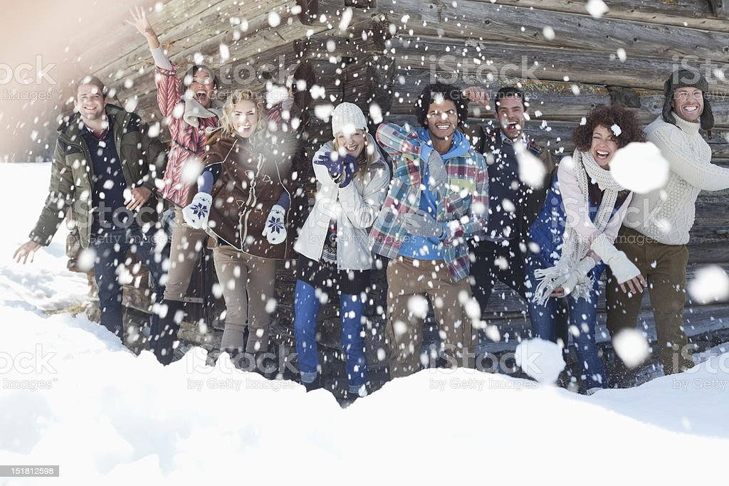 Portrait of smiling friends throwing snowballs in front of cabin stock photo