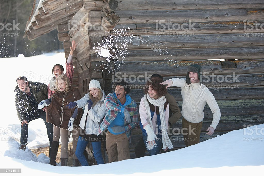 Portrait of smiling friends throwing snowballs in front of cabin royalty-free stock photo