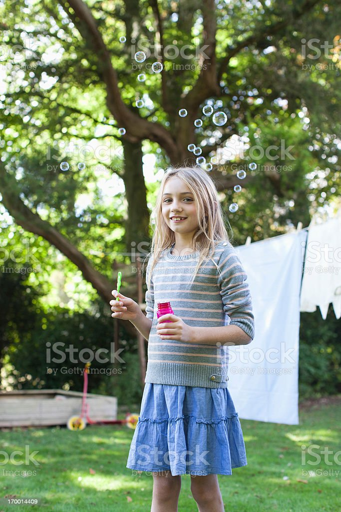 Portrait of smiling girl blowing bubbles in backyard stock photo