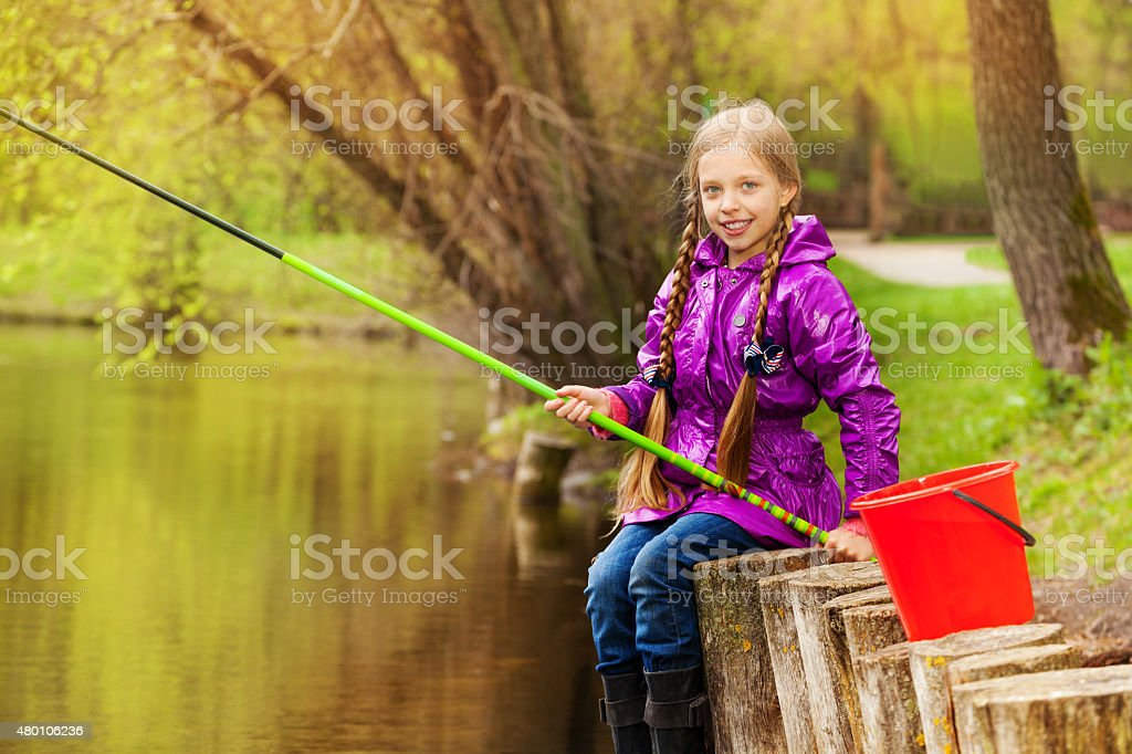 Portrait of smiling girl fishing near pond stock photo