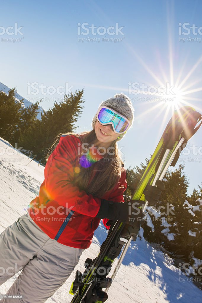 Portrait of smiling girl with skis looking at camera. stock photo