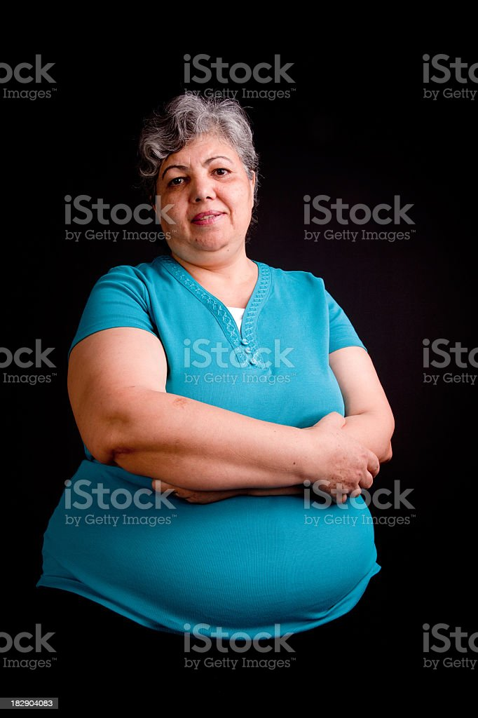 Portrait of smiling grey-haired woman in black background royalty-free stock photo