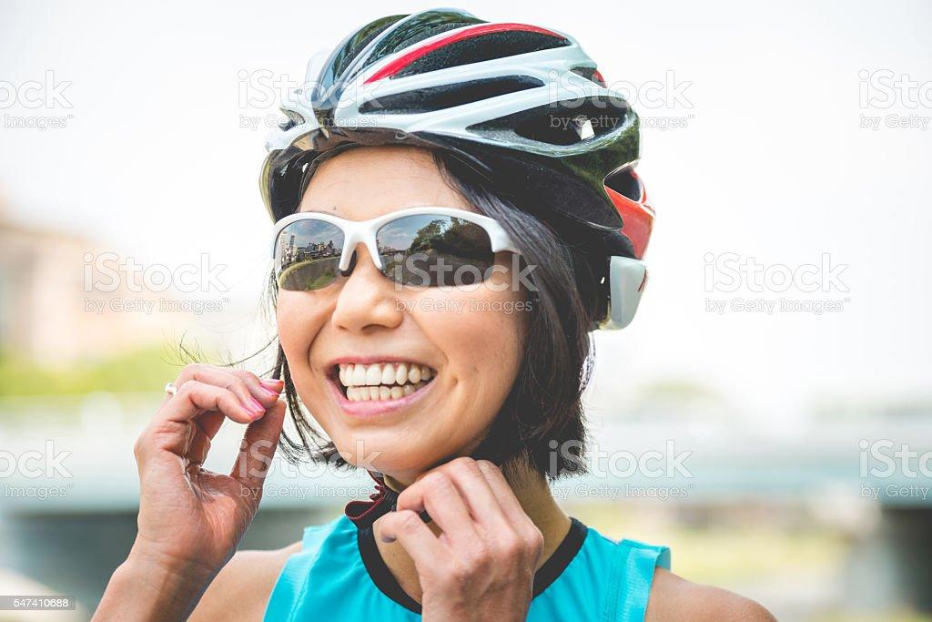 Portrait of Smiling Japanese Woman Fastening Helmet in Kyoto, Japan stock photo