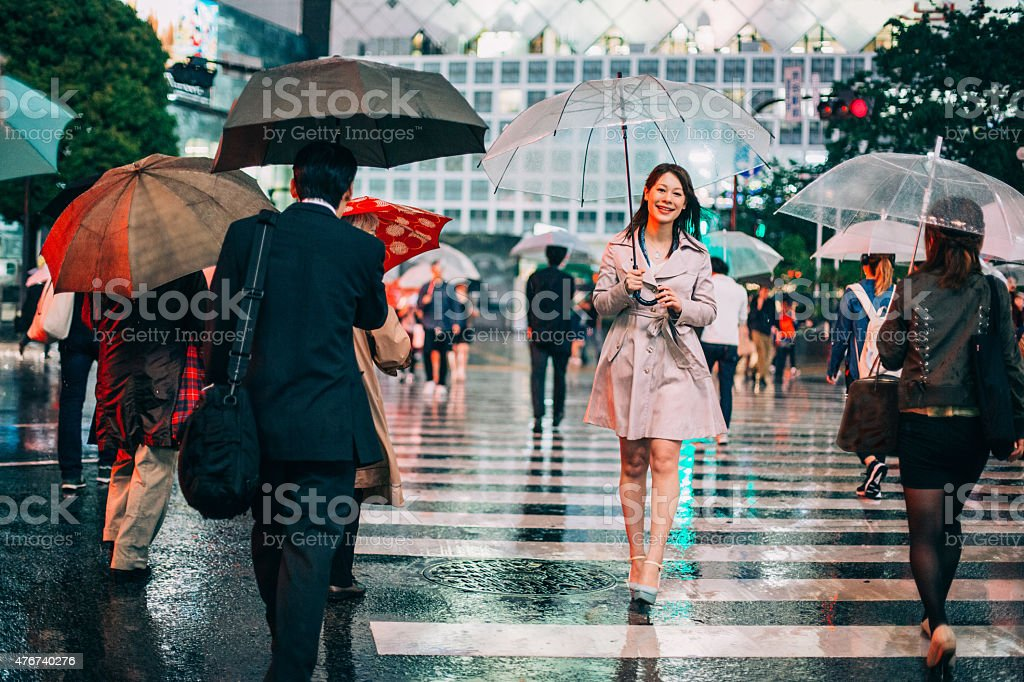Portrait of smiling japanese woman walking in the rain stock photo