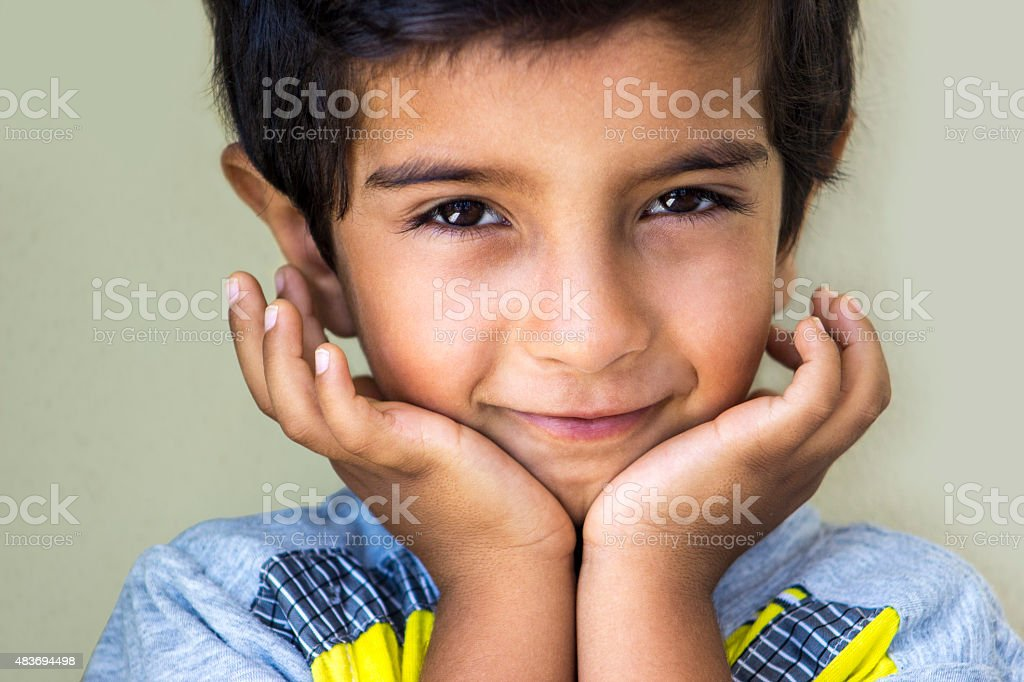 Portrait of smiling little boy hands on chin stock photo