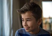 Portrait of smiling little boy watching outside from window