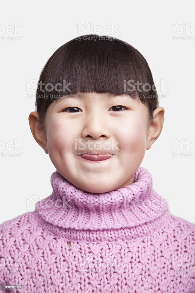 Portrait of smiling little girl sticking tongue out, studio shot royalty-free stock photo