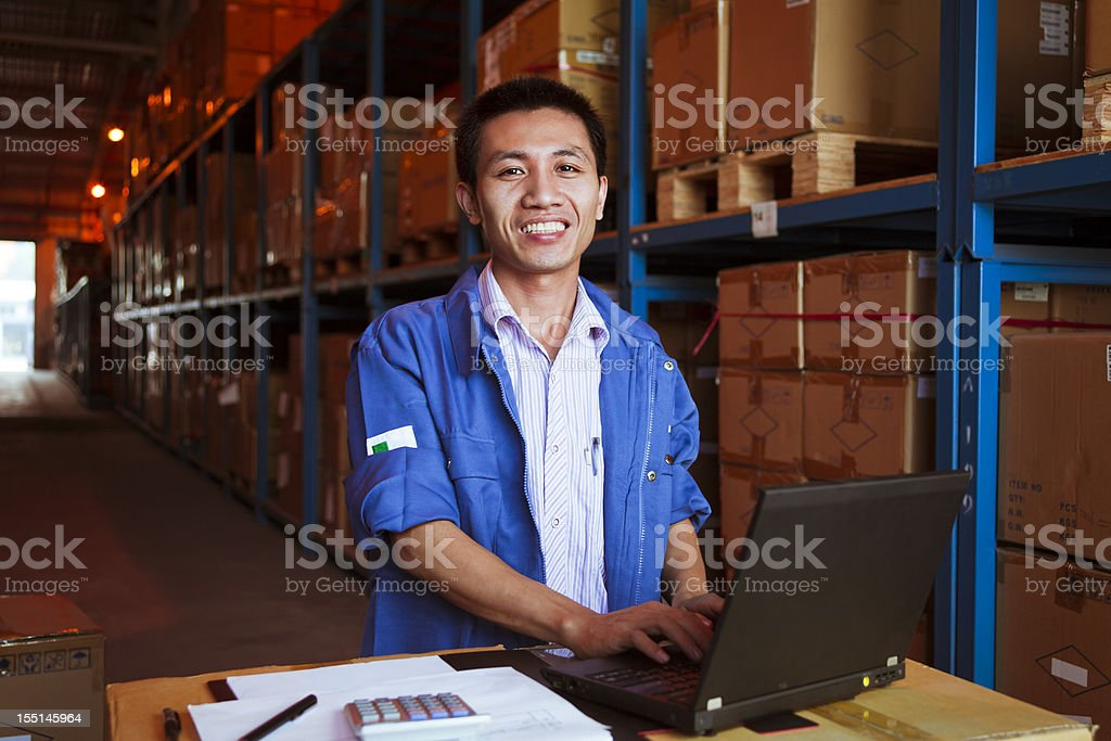 Portrait of smiling male warehouse worker using a laptop royalty-free stock photo