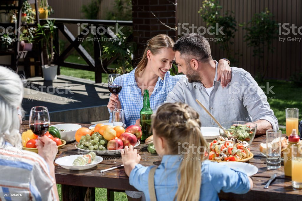 portrait of smiling man and woman sitting at table with family near by stock photo