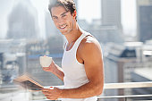 Portrait of smiling man drinking coffee and reading newspaper on urban balcony