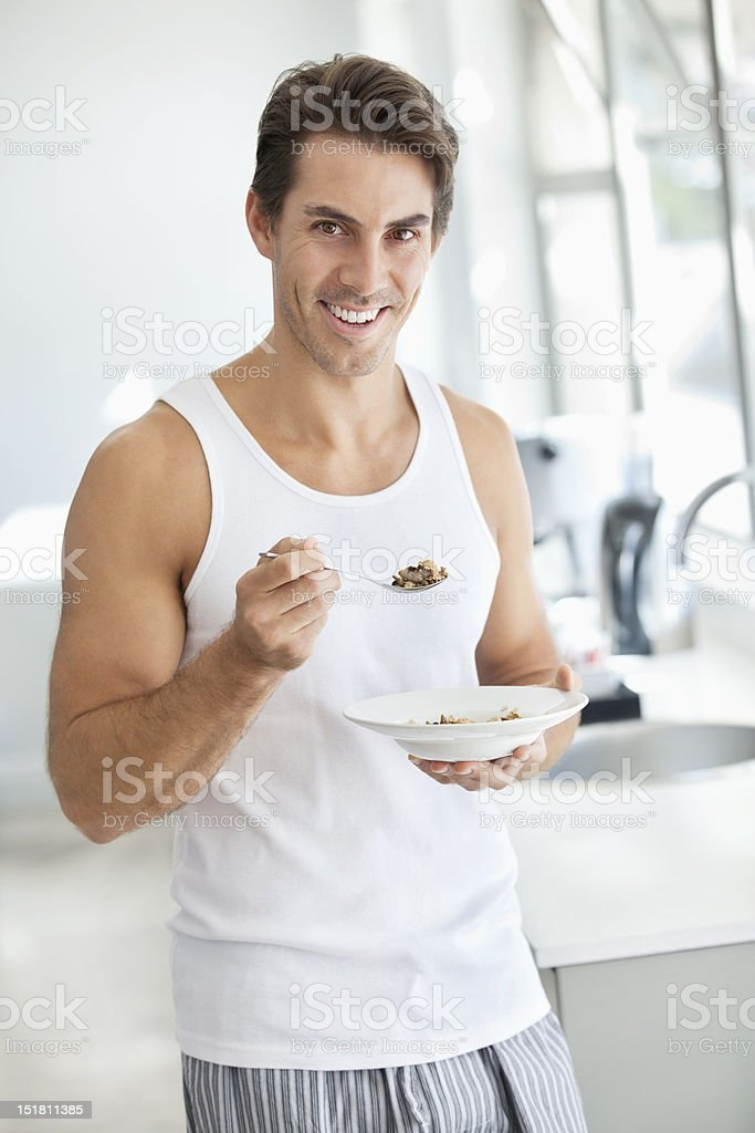 Portrait of smiling man eating cereal in kitchen royalty-free stock photo