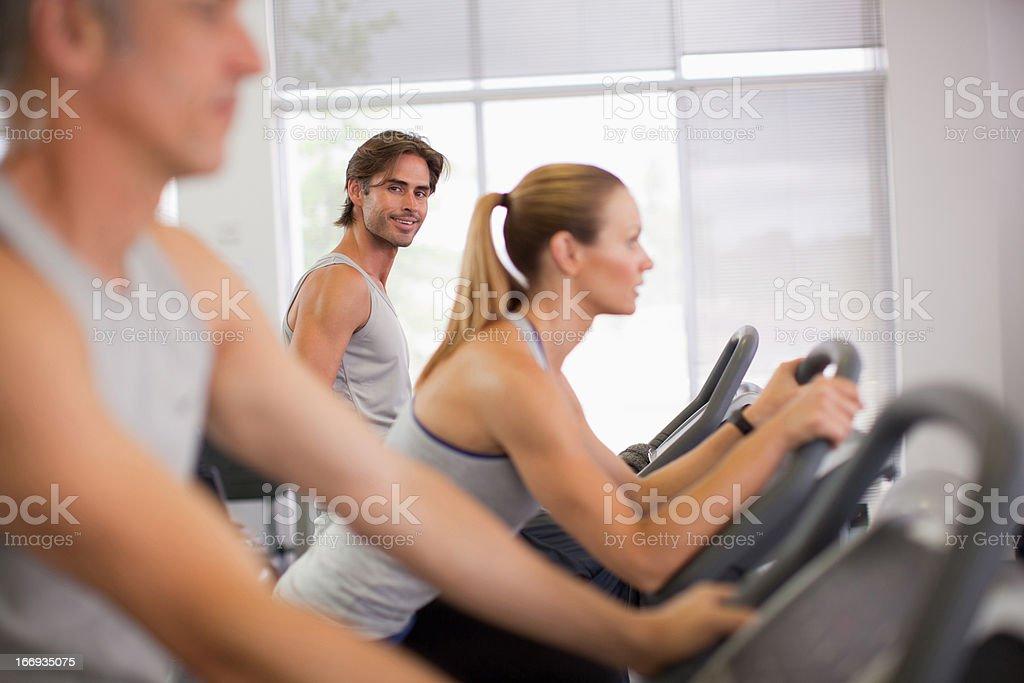 Portrait of smiling man on exercise bike in gymnasium royalty-free stock photo