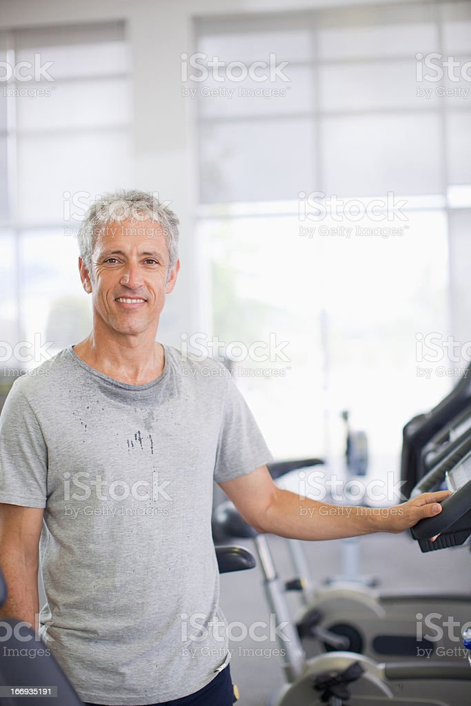 Portrait of smiling man on treadmill in gymnasium royalty-free stock photo