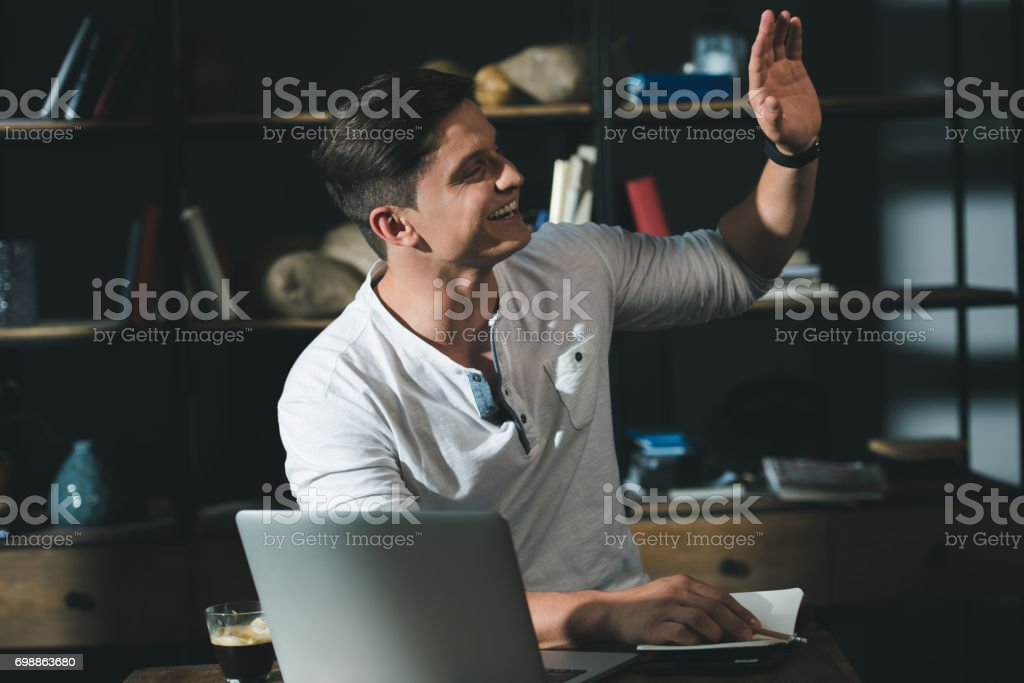 Portrait of smiling man sitting at the table with laptop and waving by hand to somebody aside stock photo