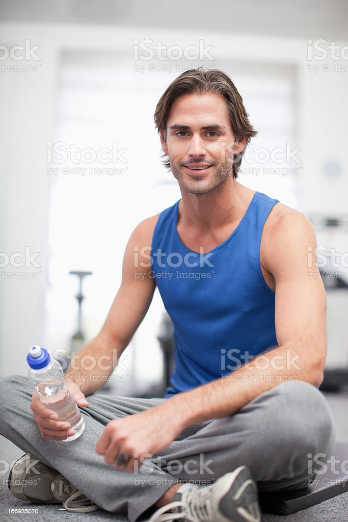 Portrait of smiling man sitting on exercise mat in gymnasium royalty-free stock photo