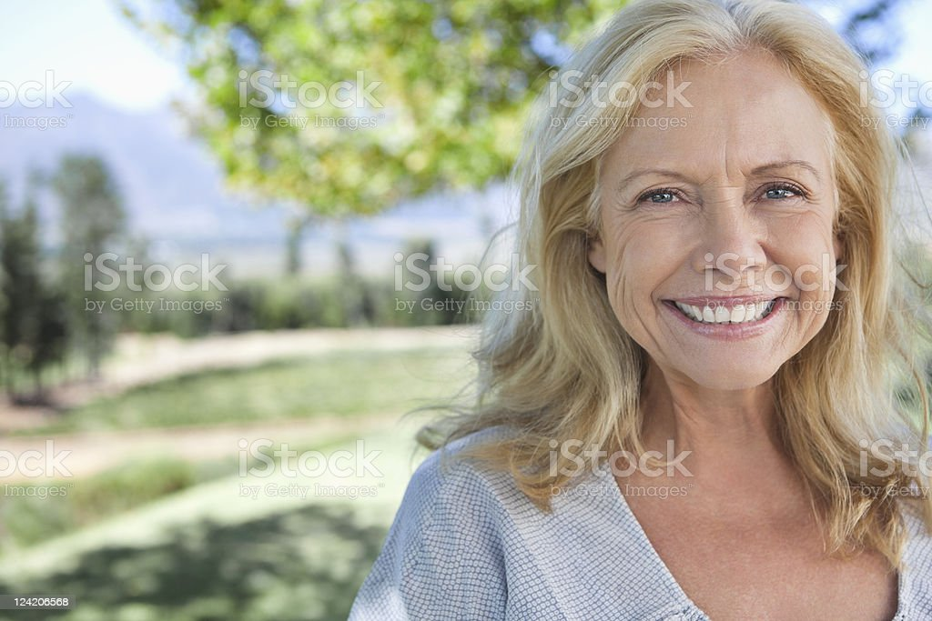 Portrait of smiling mature woman in park stock photo