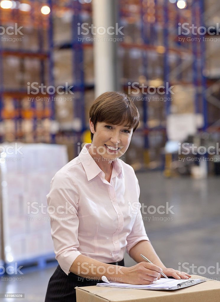 Portrait of smiling mature woman working in warehouse stock photo