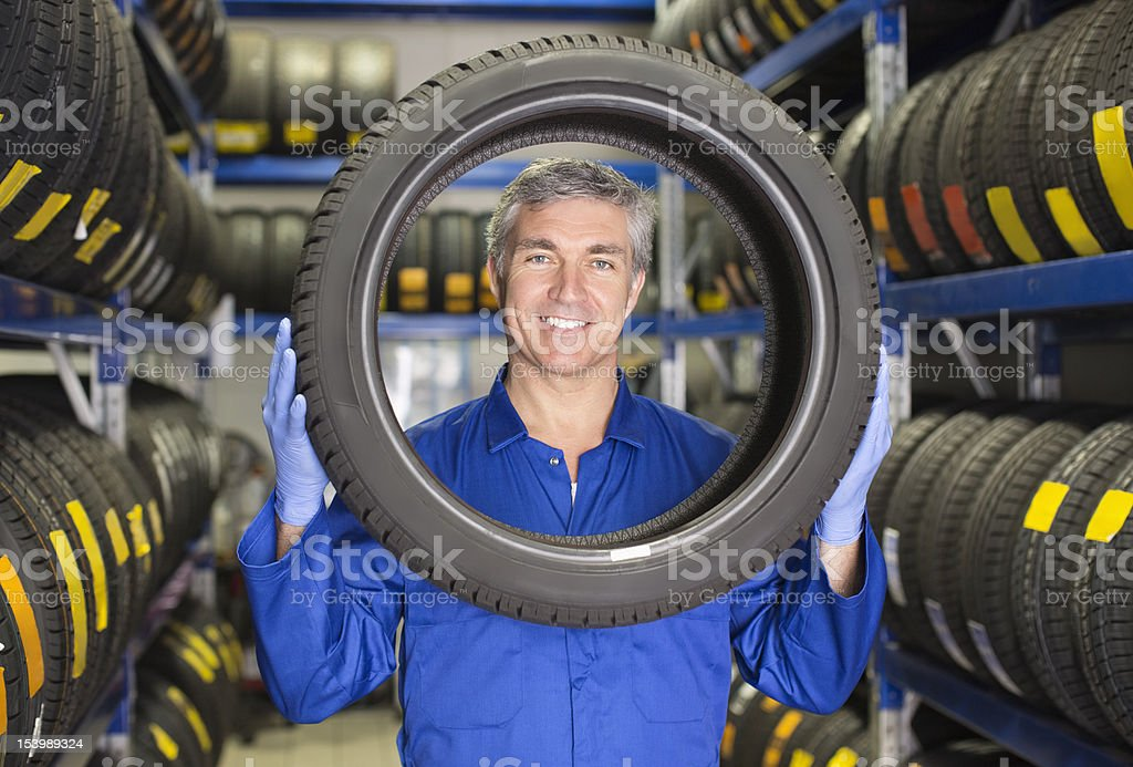Portrait of smiling mechanic holding tire in auto repair shop royalty-free stock photo