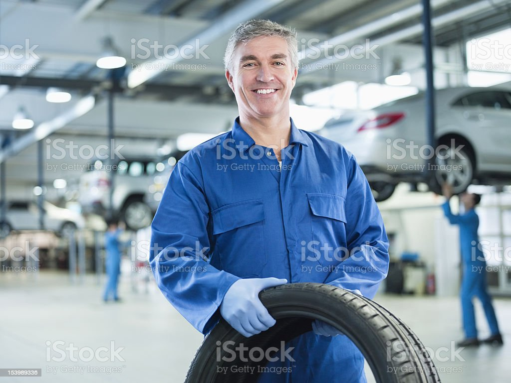 Portrait of smiling mechanic holding tire in auto repair shop stock photo