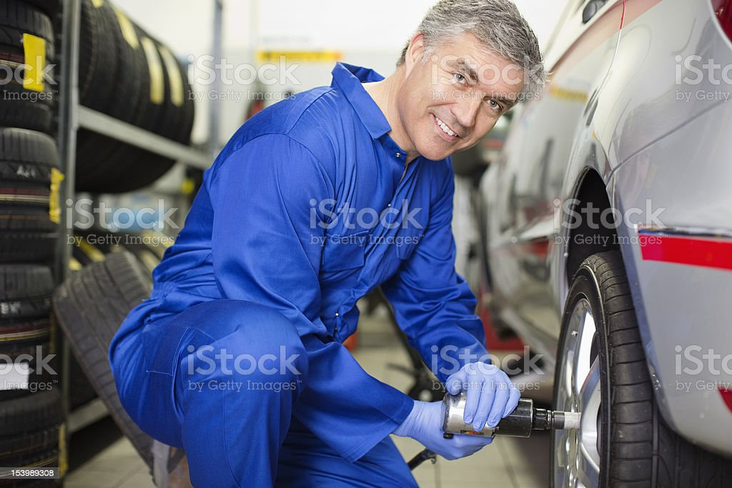 Portrait of smiling mechanic tightening lug nuts on car in auto repair shop royalty-free stock photo
