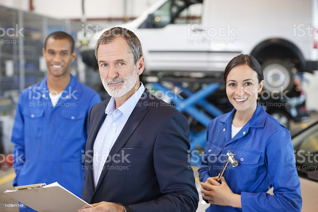 Portrait of smiling mechanics and businessman in auto repair shop royalty-free stock photo