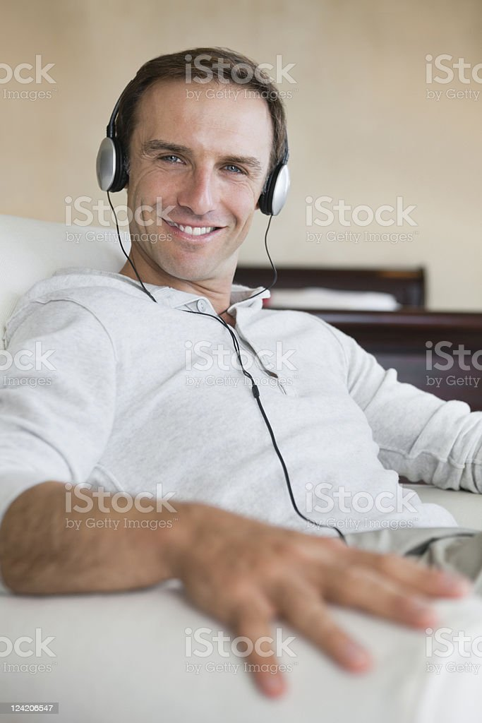 Portrait of smiling mid adult man listening to music on headphones at home royalty-free stock photo