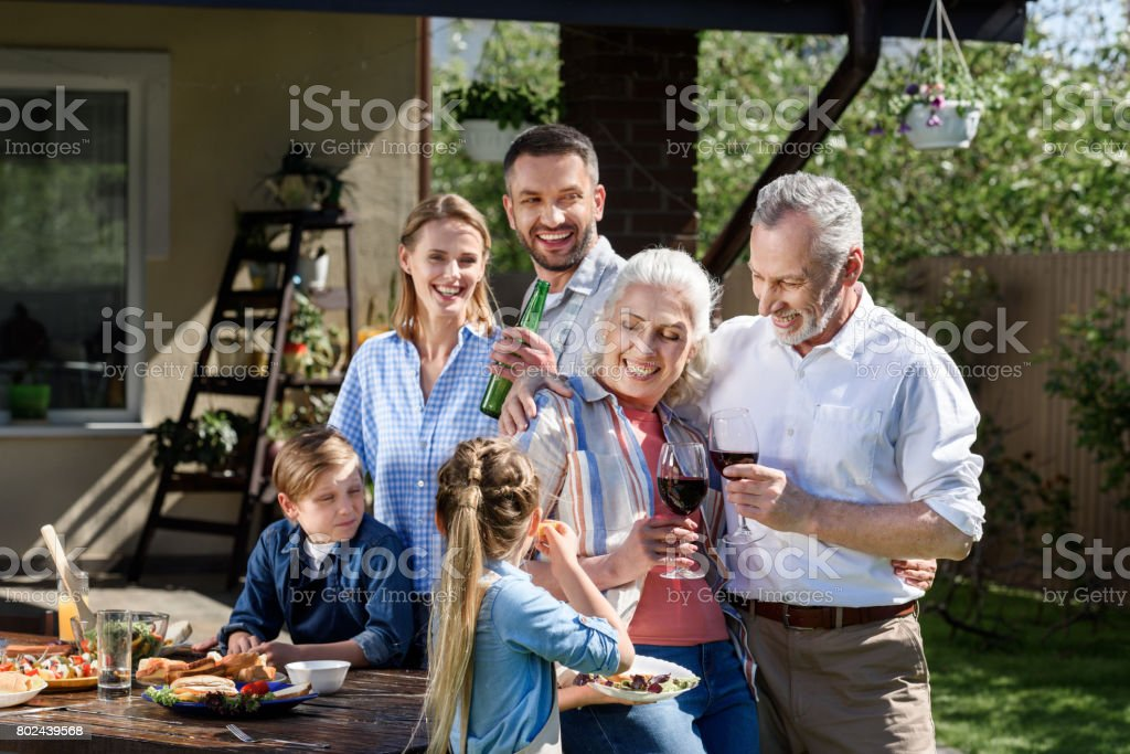Portrait of smiling multi-generational family having picnic on patio at daytime stock photo